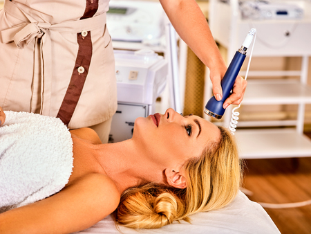 Ultrasonic facial treatment on ultrasound face machine. Woman has electric lift massage spa salon. Stimulation female forehead muscles. Professional equipment microcurrent therapy in hand. Stock Photo