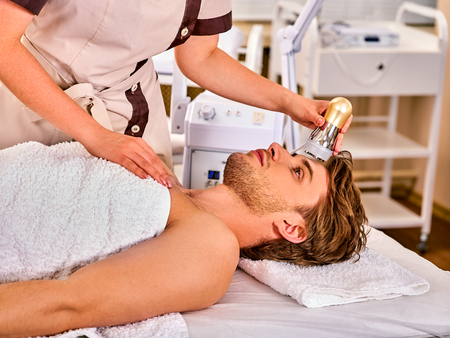 Skin resurfacing facial procedure on gold ultrasound face machine. Man receiving electric lift massage at spa salon. Electronic stimulation male muscles. Modern technologies Indoor. Stock Photo