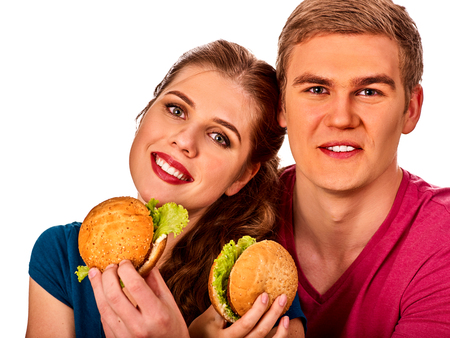 beefburger: Couple eating in fast food restaurant. Man and woman eat hamburger with ham . Friends holding two burder junk on white background isolated.