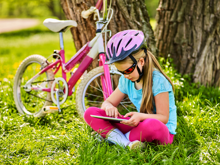 Child traveling bicycle in summer park. Bicyclist little girl watch on tablet computer. Kid in helmet counts pulse after sport training and is looking for way to navigator. Stock Photo