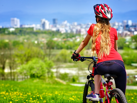 Bicycle girl has rest. Woman wearing sport helmet rides returns into city. Cycling is good for health. Cyclist is looking at city in distance. Stock Photo