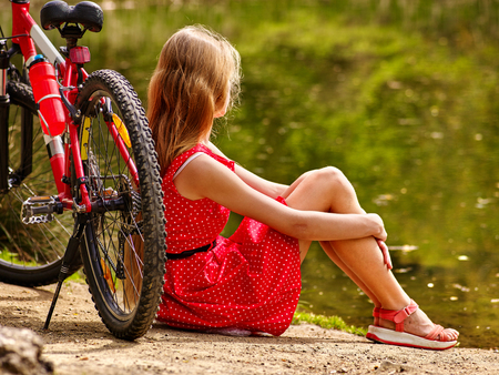 admires: Bicycle girl wearing red polka dots dress admires pond into park. Woman sitting on green grass near water in summer park. Stock Photo