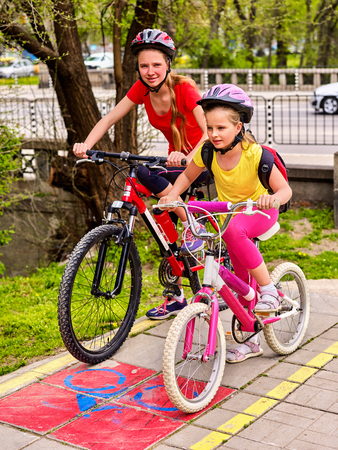 Bicycle path and sign with children. Girls wearing bicycle helmet with rucksack ciclyng ride. Kids are on yellow bike lane . Alternative to urban transport. Bike share program save money and time.