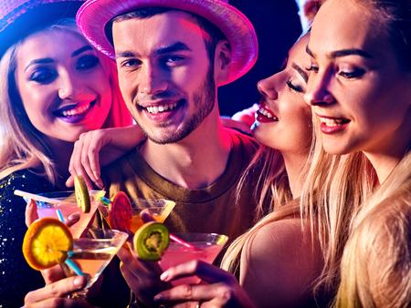Soirée dansante avec les gens du groupe de danse. Les femmes et les hommes ont un cocktail amusant et martini boire avec des fruits en boîte de nuit. Heureux homme en chapeau de premier plan.