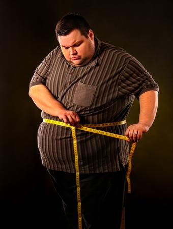 Grasa del vientre del hombre con la pérdida de peso de la cinta métrica alrededor del cuerpo en fondo negro. Primer día de dieta. La persona va a perder peso.
