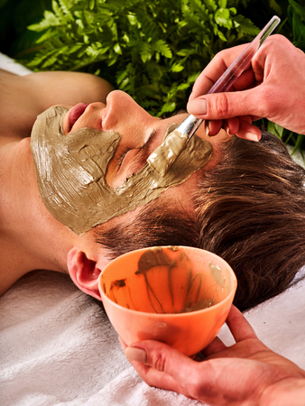 Mud facial mask of man in spa salon. Massage with clay full face. Girl on with therapy room. Man lying wooden spa bed. Beautician with bowl therapeutic procedure isolated background. Close-up of a mans face. Stock Photo