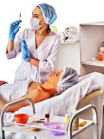 dermal: Filler injection for male forehead face. Plastic aesthetic facial surgery in beauty clinic. Folded towels in the background. Close up of doctor in medical gloves with syringe injects nasolabial fold drug Stock Photo