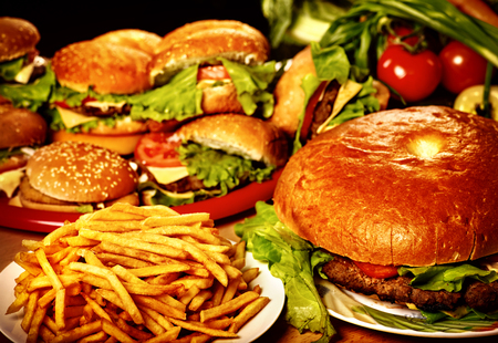 Fast food for large group friends. Unhealthy hamburger and french fries on plate for very hungry group people. Фото со стока