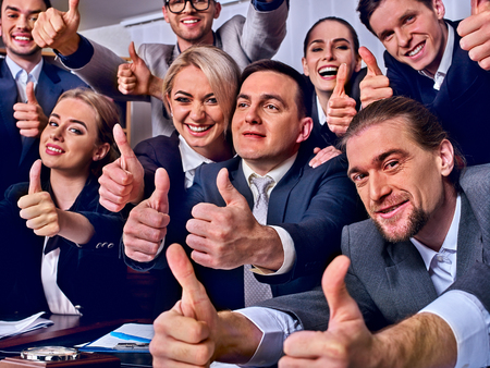 Business people office life of team people happy sitting table . People in business suits are happy from successful deal and wish success to everyone around them and gesture show thumb up. Stock Photo