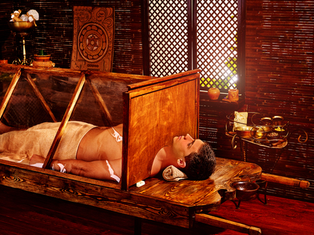 Man having Ayurvedic sauna treatment. Indian steam detoxification of male body. Study of Indian culture.