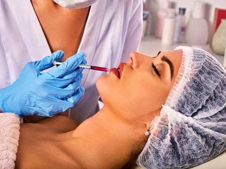 dermal: Filler injection for female forehead face. Plastic aesthetic facial surgery in beauty clinic. Silicone lips in the girl. Doctor in medical gloves with syringe injects lips augmentation.