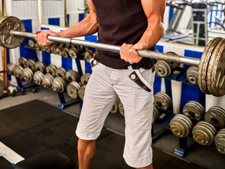 sholders: Man dumbell workout in gym. Muscle male working with dumbbells his body at gym. Top view of handsome sportsman. Doing sports to maintain health in gym. Student decided to engage in fitness.