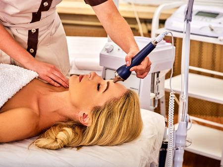 specials: Ultrasonic facial treatment on ultrasound face machine. Woman has electric lift massage spa salon. Stimulation muscles by professional equipment microcurrent therapy. Modern methods of rejuvenation.