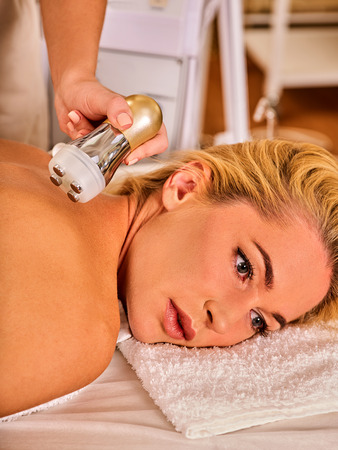 resurfacing: Skin resurfacing body procedure on gold ultrasound face machine. Woman receiving electric lift body massage at spa salon. Electronic stimulation muscles. Modern technologies and methods rejuvenation.