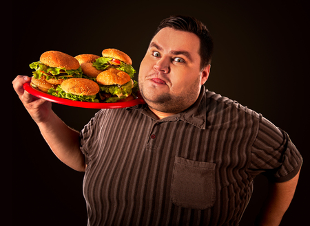 Fat man eating fast food hamberger and carries treat for friends on tray. Breakfast for overweight person. Junk meal leads to obesity. Person regularly overeats concept on black background. Fatso with a tray of harmful food.
