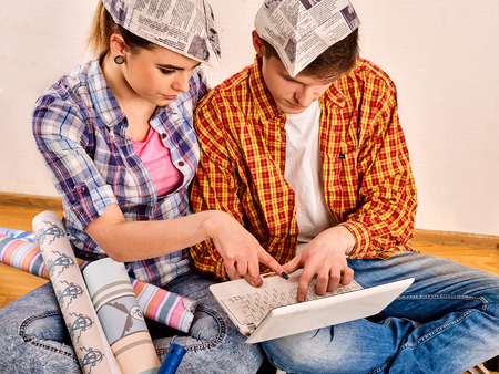 Repair family by happy couple building home using white laptop. Woman and man in newspaper cap renovation apartment.
