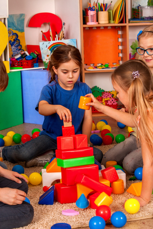 Break school of children playing in kids cubes indoor. Two girl together play on soft carpeton floor. Vertical shot.