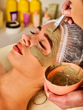 Mud facial mask of woman in spa salon. Massage with clay full face. Girl on with therapy room. Female lying wooden spa bed. Beautician with brush therapeutic procedure isolated background. Home mask. Stock Photo