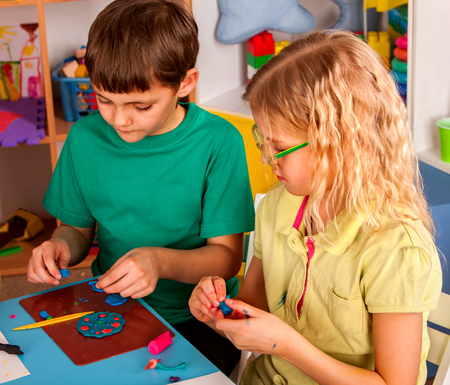 sculp: Plasticine modeling clay in children class. kids together play dough and mold from plasticine in kindergarten or preschool. Group of four people. Teaching modeling.