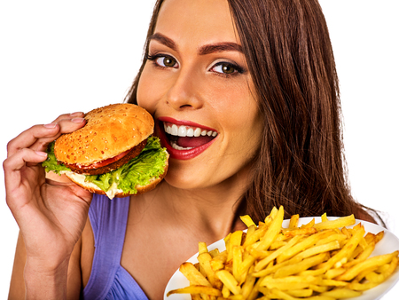 school cafeteria: Woman eating french fries and hamburger. Portrait of student consume fast food on table. Girl trying to eat junk. Advertise fast food on daek background. Girl is having supper after hard days work.