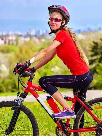 Échapper à l'urbain. La fille de bicyclette se repose de l'agitation de la ville. Femme portant des casques de casque de sport retourne dans l'urbanisation. Respect de l'environnement Tuyaux d'usine en arrière-plan.