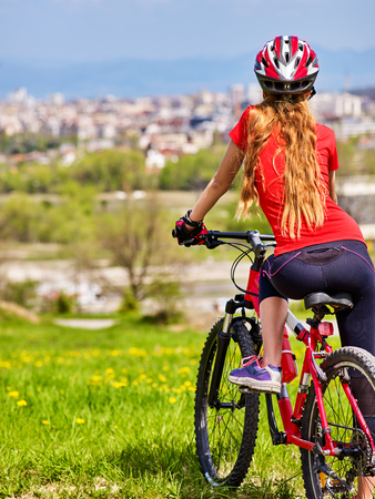 Escape urban . Bicycle girl has rest from city bustle. Woman wearing sport helmet returns home after long hike in urbanization . Respect for environment. Factory pipes in background. Back view. Stock Photo