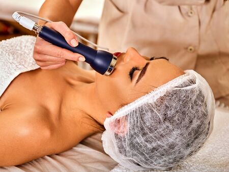 Ultrasonic facial treatment on ultrasound face machine. Woman has electric lift massage spa salon. Stimulation muscles on equipment microcurrent therapy . Modern technologies and methods rejuvenation.