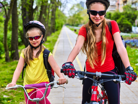 Bicycle path with children. Girls wearing bicycle helmet with rucksack ciclyng ride. Kids or mother with daughter are on yellow bike lane. Alternative to urban transport. Flowerbed with flowers in background. Children for a walk.