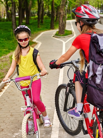 Bicycle path and sign with children. Girls wearing helmet with rucksack ciclyng ride. Kids are on white bike lane. Alternative to urban transport. Oncoming traffic. People support healthy lifestyle. Stock Photo