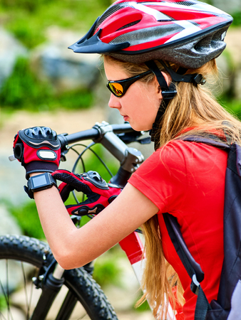 Woman on bicycle ride mountain. Girl with smart watch traveling in summer park. Cycling person with rucksack counts pulse after sport training . Girl does not forget about gadgets even in campaign.