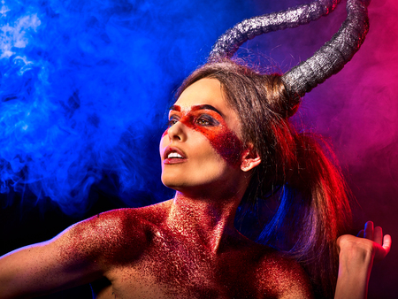 Mad satan woman on black magic ritual of in hell . Witch reincarnation mythical creature on Sabbath. Devil absorbing soul Halloween. Zodiac Capricorn Aries , Taurus astrology. Make-up for night club. Stock Photo
