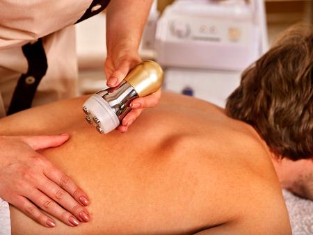 Man back massage beauty salon. Electric stimulation man skin care . Professional medical equipment microcurrent body lift . Anti aging rejuvenation . Man receiving electroporation skin care therapy .