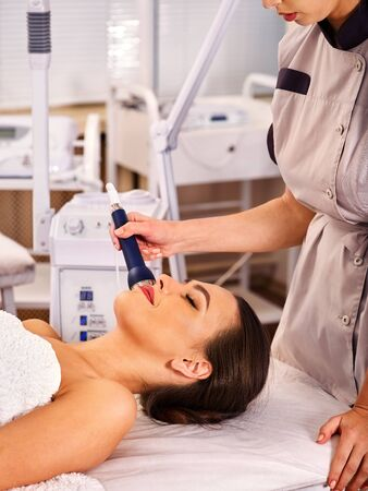 specials: Ultrasonic facial treatment on ultrasound face machine. Woman has electric lift medical massage spa salon. Stimulation muscles by microcurrent therapy. Modern methods of rejuvenation.