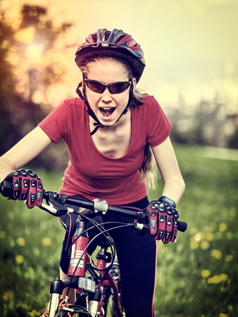 Woman traveling bicycle in summer park. Girl in helmet road bike for running on green grass in summer morning. Cycling trip is good for health. Tone shiny background. Stock Photo