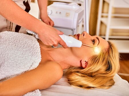 high frequency: High frequency machine in spa salon. Young woman receiving electric darsonval facial massage after procedure at beauty room close up. Removal of acne from surface of face.