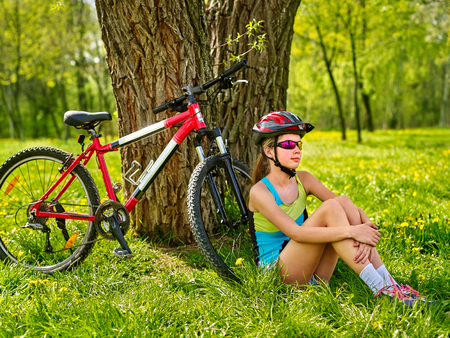 Girl traveling bicycle in summer park. Bicyclist has rest near bike. Cycling is good for health in summer and spring. Girl is waiting for guy on date. Stock Photo