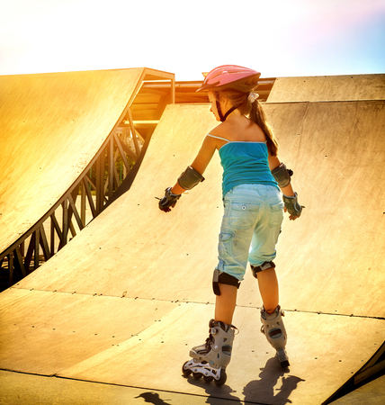 rollerskates: Girl riding on roller skates in skatepark. Backlit on background. View from back of kid. Therapeutic exercise for slimming children. Color tone.