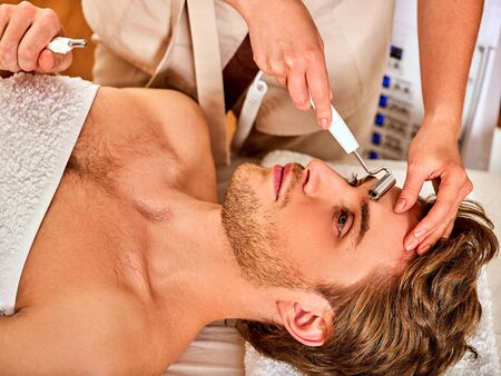 Facial massage at beauty salon. Electric stimulation skin care of man. Equipment for microcurrent lift face. Anti aging face and neck rejuvenation non surgical treatment indoor. Improvement of skin. Stock Photo