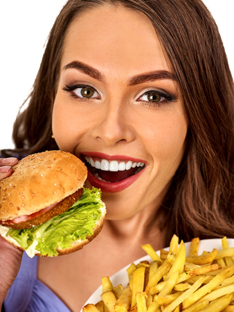 Woman eating french fries and hamburger. Portrait of student consume fast food on table. Girl trying to eat junk. Girl is having supper after hard days work. Person broke off from diet. Stock Photo