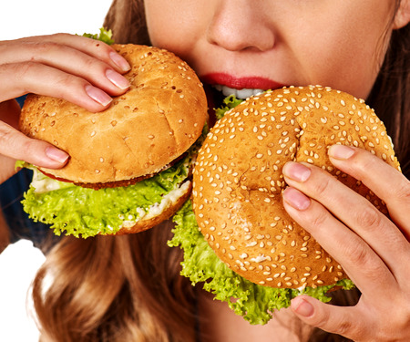 school cafeteria: Woman eating french fries and hamburger. Portrait of student consume fast food on table. Girl trying to eat junk. Cropped shot of girl is suffering from gluttony.