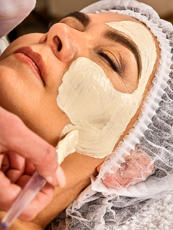 Collagen face mask. Facial skin treatment. Face of woman of elderly woman 50-60 years old receiving cosmetic procedure in beauty salon close up . Professional beautician. Removing wrinkles. Stock Photo