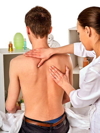 luxacion: Shoulder and neck massage for woman in spa salon. Doctor making neck therapy in rehabilitation center . Direction of dislocation in clinic. Reinforcement of joint in good clinic. Back view.
