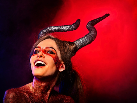 Mad satan woman on black magic ritual of in hell . Witch reincarnation mythical creature on Sabbath. Devil with soul Halloween. Zodiac astrology. Make-up for night club. Black magic on red background. Stock Photo