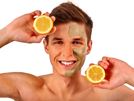 Facial mask from fresh fruits and clay for man concept. Face with treatment mud applied . Male holding lemon half for skin care procedure in salon. Lemon main ingredient in cosmetic masks isolated. Stock fotó