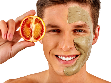 applied: Facial mask from fresh fruits and clay for man concept. Face with treatment mud applied. Male holding lemon half for skin care procedure in salon. Man smiles dazzlingly on isolated. Stock Photo