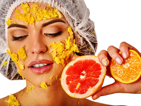 green been: Facial mask from fresh fruits for woman. Girl in medical hat bit slices of kiwi and hold plate with fruit salad. Green plants on backgrounds in spa salon. Traditional medicine has been widely used.