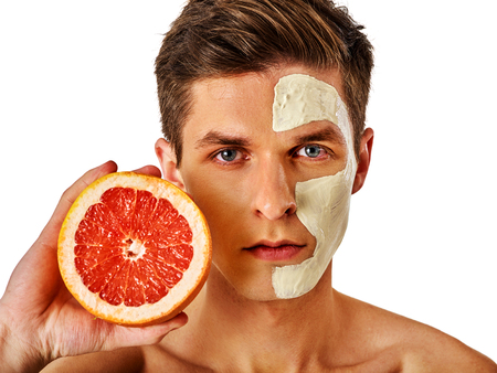 applied: Facial mask from fresh fruits and clay for man concept. Face with treatment mud applied . Male holding grapefruit half for skin care procedure salon. Grapefruit are main ingredient in cosmetic masks.