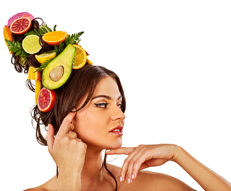 dint: Hair and facial mask from fresh fruits for woman concept. Girl care her skin homemade by dint of organic therapy on isolated. Woman in profile is testing new diet with vitamins for hair.