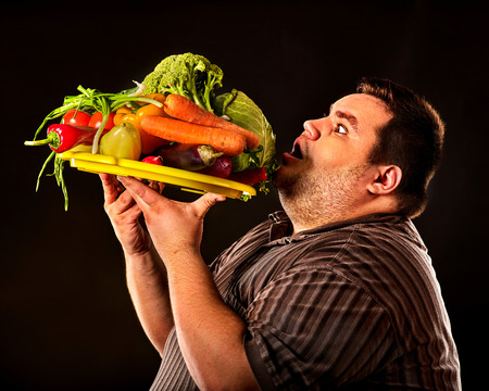 Diet fat man eating healthy food with vegetables for overweight male. Male trying to lose weight first time .Hungry person ready to eat everything. Vegetables for diet in unlimited quantities. Stock Photo