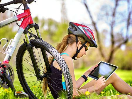 Girl rides bicycle. Girl wearing headset in cycling watch in pc tablet near bicycle. Cyclist looking pc tablet. Woman in social network communicates with friends. Adolescent is dependent on networks.